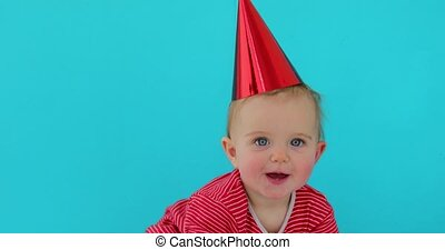 little girl in holiday cap blue background