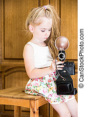 little girl in home with camera