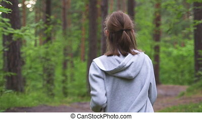 Little girl in hoodie running in the forest. Sports concept.