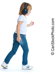 Little girl in jeans and big black headphones