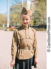 Little girl in military uniform on holiday day of victory
