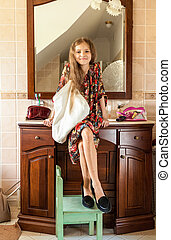 girl in mothers clothes sitting on sink at bathroom