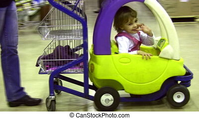 Little girl in moving shopping cart car