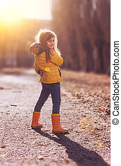 Little girl in orange jacket and rubber boots