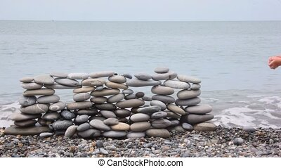 little girl in panama put pebble on wall of stones on beach, sea in background