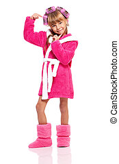 Pretty little girl in pink bathrobe with curlers on her head on white background