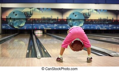 Little girl in pink clothes play bowling and jumps