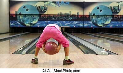 Little girl in pink clothes throws bowling ball and runs away
