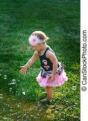 Little girl in pink dress blowing soap bubbles on summer...