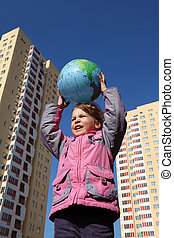 little girl in pink jacket holds in her hands above head balloon in form of globe. In background of multi-storey yellow house