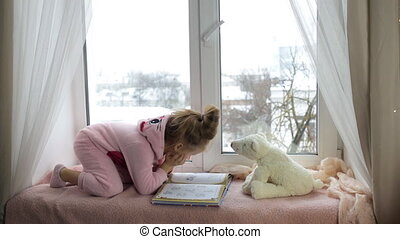 Little girl in pink pajamas reading a book sitting on the...