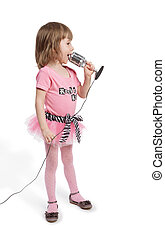 Little girl in pink with microphone stands in full-length half-turned and sings.