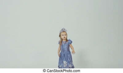 Little girl in princess costume jumping in studio on white background in slow motion