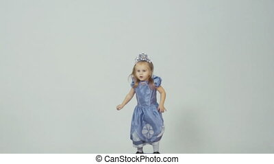 Little girl in princess costume jumping in studio on white...