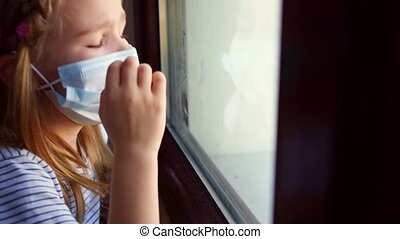 a little girl in a protective mask, look out of the window outside. she is sick and self-isolating during the pandemic.