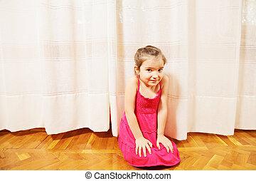 Little girl in red dress on floor