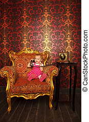 Little girl in red dress talking vintage phone. Interior in retro style. Against ornamental wallpaper.