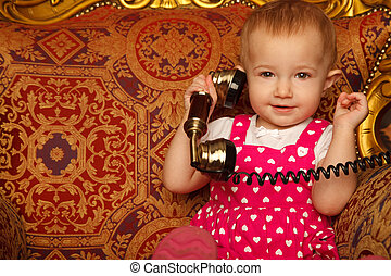 Little girl in red dress talking vintage phone. Interior in ...
