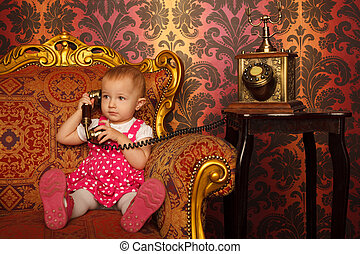 Little girl in red dress talking vintage phone. Interior in retro style. Horizontal format.