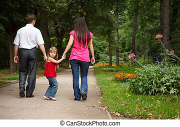 Little girl in red dress together with parents walks in...