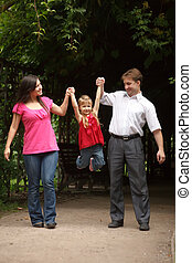 Little girl in red dress with father and mother in park. Girl plays being shaken on hands of parents.