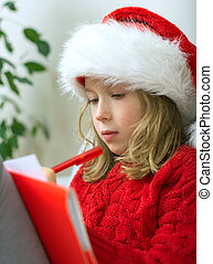 Little girl in red hat writing a letter to Santa Claus.