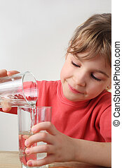 little girl in red shirt pour out water from one glass to other, half body, vertical