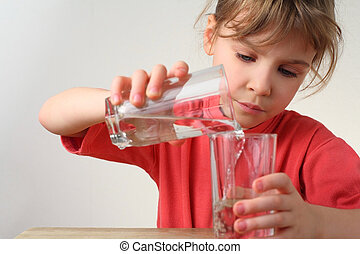 little girl in red shirt pour out water from one glass to other, half body