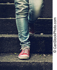 Little girl in red sneakers and jeans standing on the stairs...