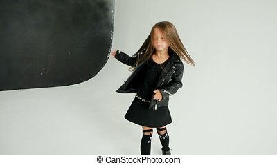 little girl in rocker style throws hat over