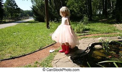 Little girl in rubber boots in a flower garden.