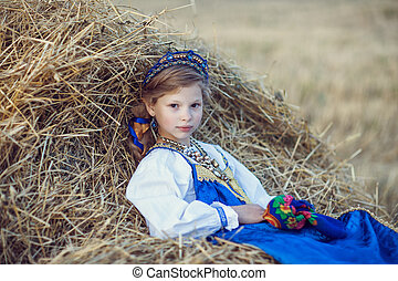 Rural themes. Girl in the national Slavic costume. He lies on a stack of straw in the field. On his head a wreath of white flowers. White shirt