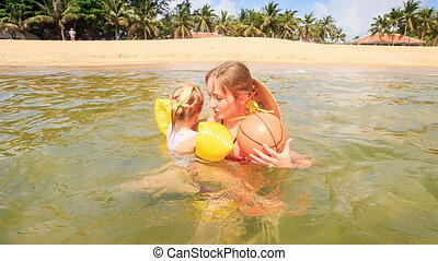 Little Girl in Safety Armbands Mother Play with Ball in Sea