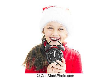 little girl in Santa Claus hat holding alarm clock showing twelv