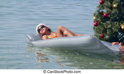 Little girl in Santa hat floating on inflatable air mattress near Christmas tree