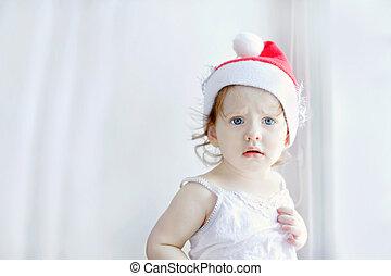 Little girl in santa hat, on a light background near the window