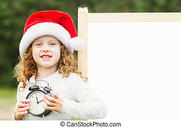 Little girl in Santa hat with clock. Girl at blackboard. Place