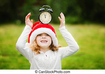 Little girl in Santa hat with clock have a Christmas.