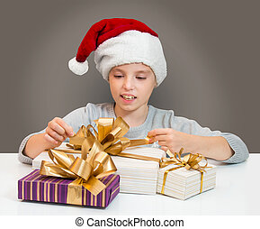 Little girl in Santa hat with gift box for Christmas.