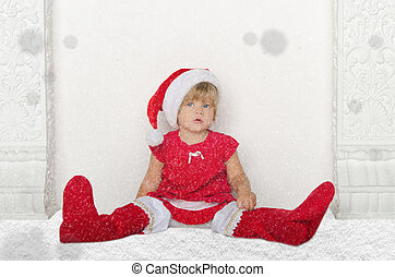 Little girl in Santa suit sitting on floor with snow