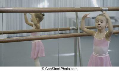 Little girl in skirt is spinning near wooden ballet machine....