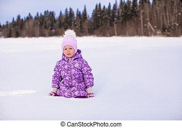 Little girl in snow winter sunny day
