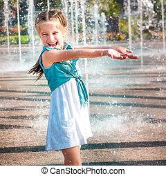 little girl in splashes a fountain - little cute girl having...