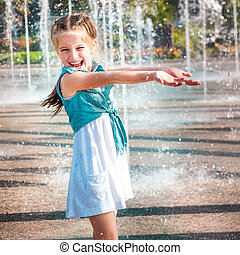 little girl in splashes a fountain - little cute girl having...