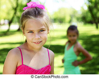 Little girl in summer park with friends
