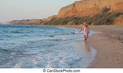 Little girl in sundress and hat running along the beach in...