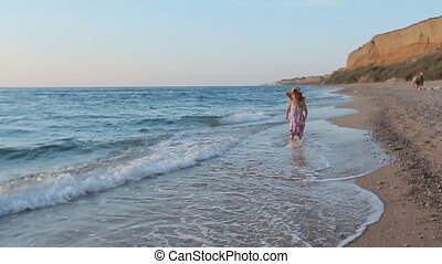 Little girl in sundress running along the sea to father and...
