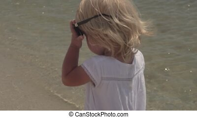 Little girl in sunglasses on the coast.