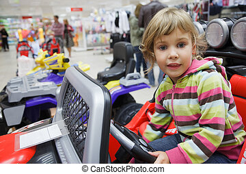 little girl in supermarket alone, chooses in department of toys. sits in an electromobile