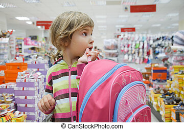 little girl in supermarket choose footwear with school bag in hands